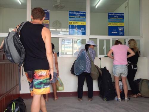 ラオス・ビエンチャンのタラートサオ・バスターミナルでバスチケットを購入する旅行者。